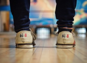 Persons feet shown standing on bowling alley
